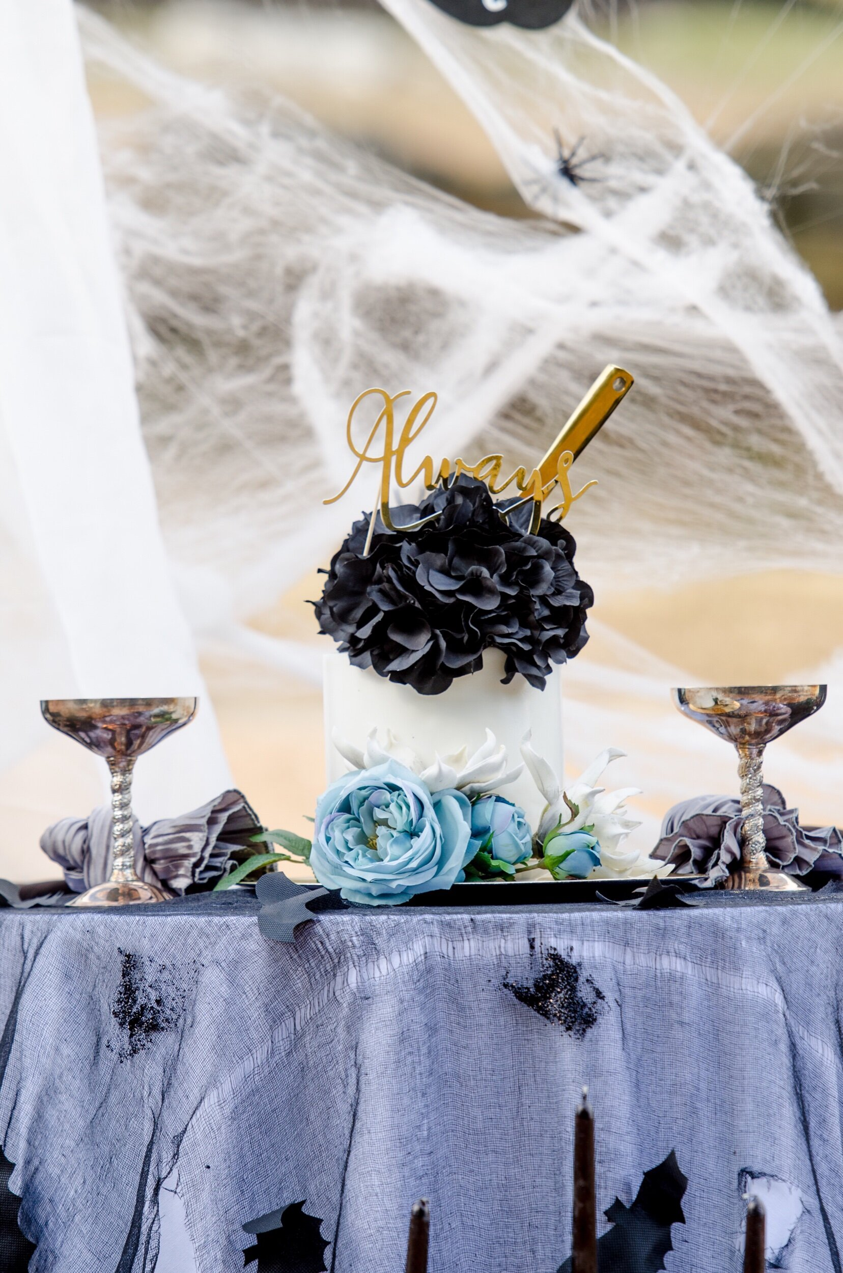The gothic wedding cake table was draped with a gauzy black cloth with attached bats, topped with gothic style wine goblets. Styled by Mint Event Design, Austin Texas party stylist