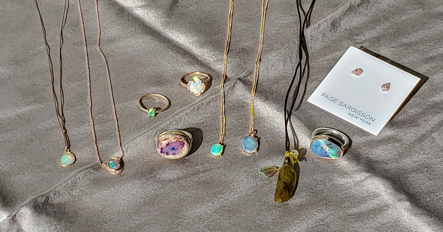 From left to right:  Margaret Solow Opal Necklace $220  Sirciam 14k Rose Gold and Opal Necklace $1610  Petite Baleine 14k Yellow Gold and Opal Ring $590  Jamie Joseph Boulder Opal Ring $1170  Sirciam 14k Rose Gold, Diamond and Opal Ring $2145  Wwake 14k Yellow Gold and Australian Opal Pendant $965  Wwake 14k Yellow Gold and Australian Opal Pendant $1305  Rene Garvey One-of-a-kind Olive Tourmaline and Ethiopian Opal Necklace $308  Jamie Joseph Opal Ring $990  Page Sargisson 18k Yellow Gold and Pink Opal Studs $185