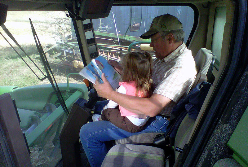 A grandpa reads to a granddaughter on lunch break during harvest.