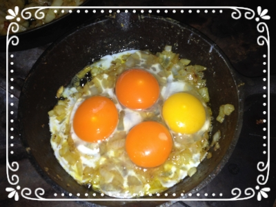 Fried onions with pastured eggs ready to be scambled. The darker eggs are chicken; the lighter egg is a duck egg.