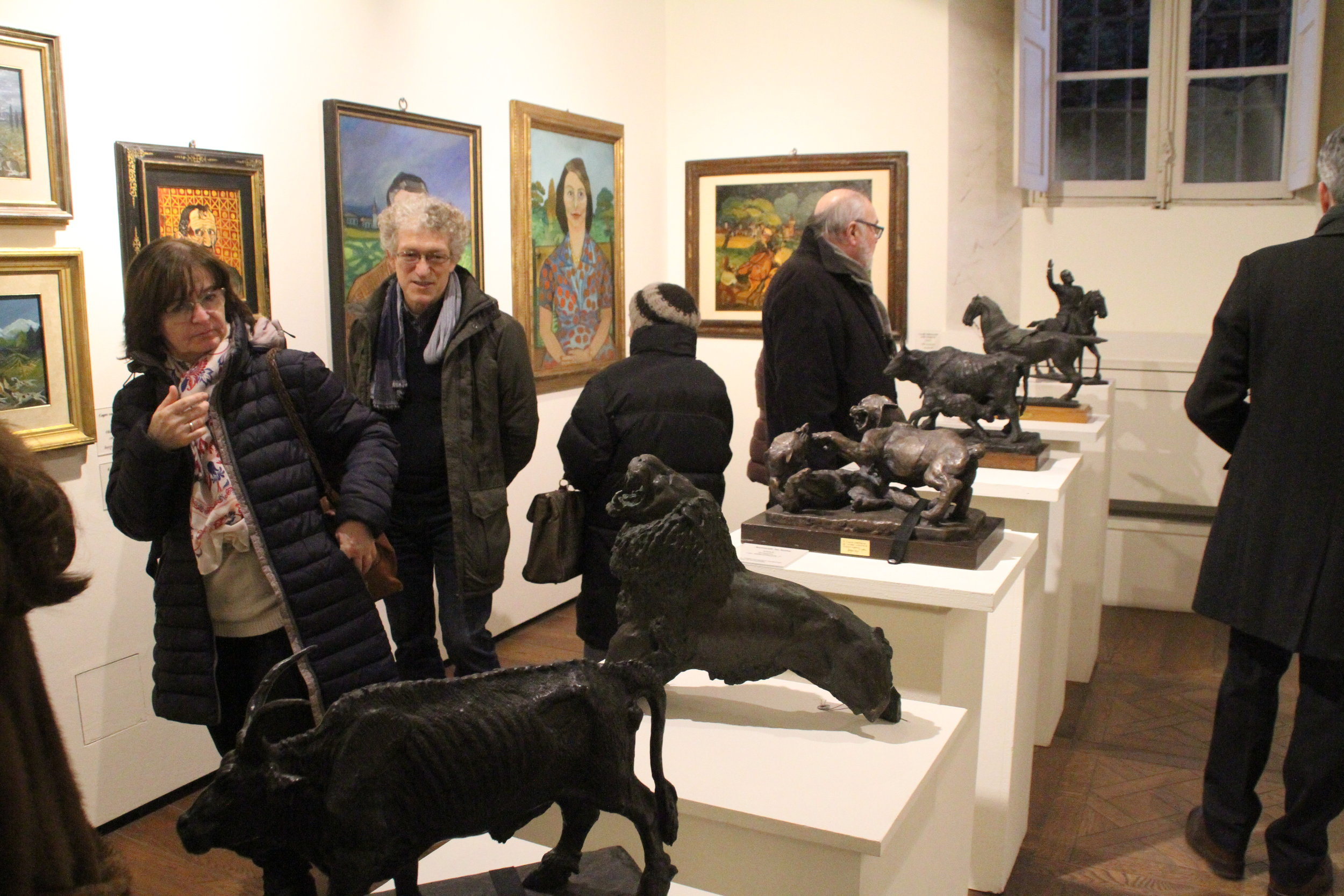 The crowd admires Antonio Ligabue's paintings and sculptures.