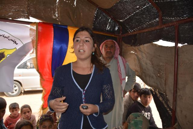 Fig 3: Eva 'Issa, Armenian representative to the Syrian Democratic Youth Council, speaks at the meeting in front of SDYC and Armenian flags. [ANHA]