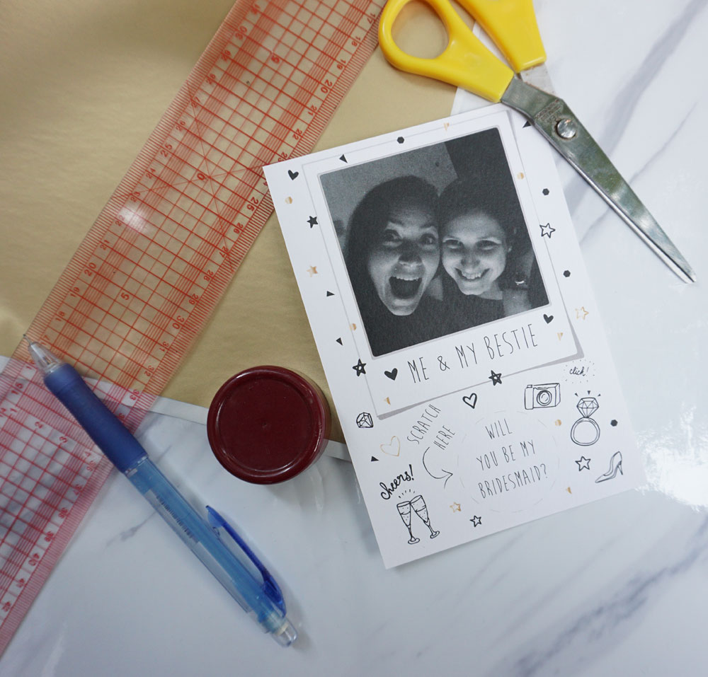 Material: - Card stock or photo paper (around 120-180 gsm)PrinterScissorsScratch-off sticker paperA base about 3.5cm wide (I used a cap from a spice dispenser)PencilPhoto of you & your bridesmaid-to-be