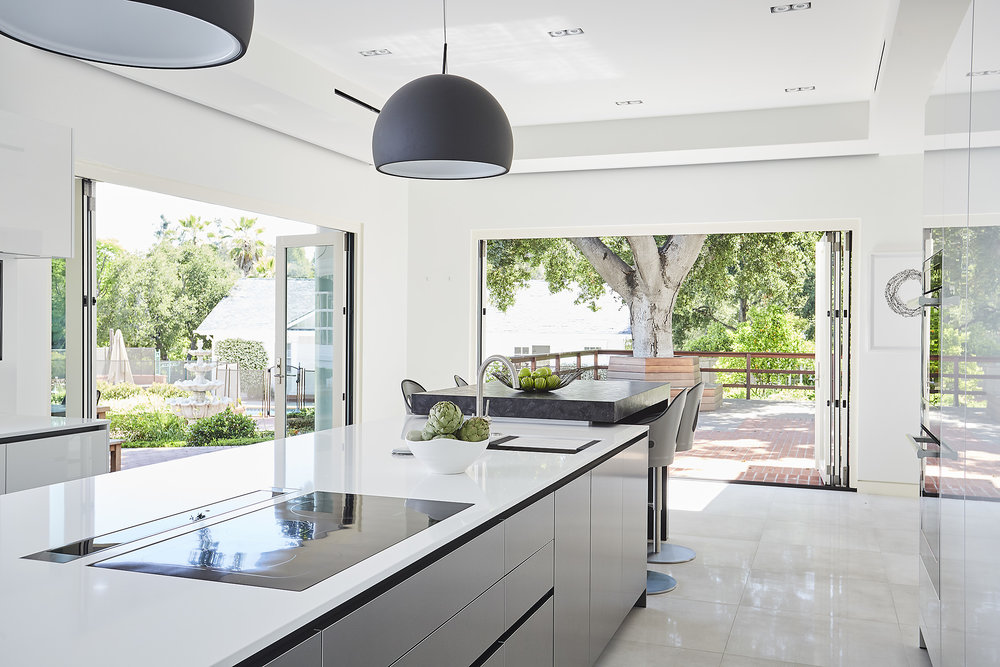 Modern kitchen with large doors open letting air in