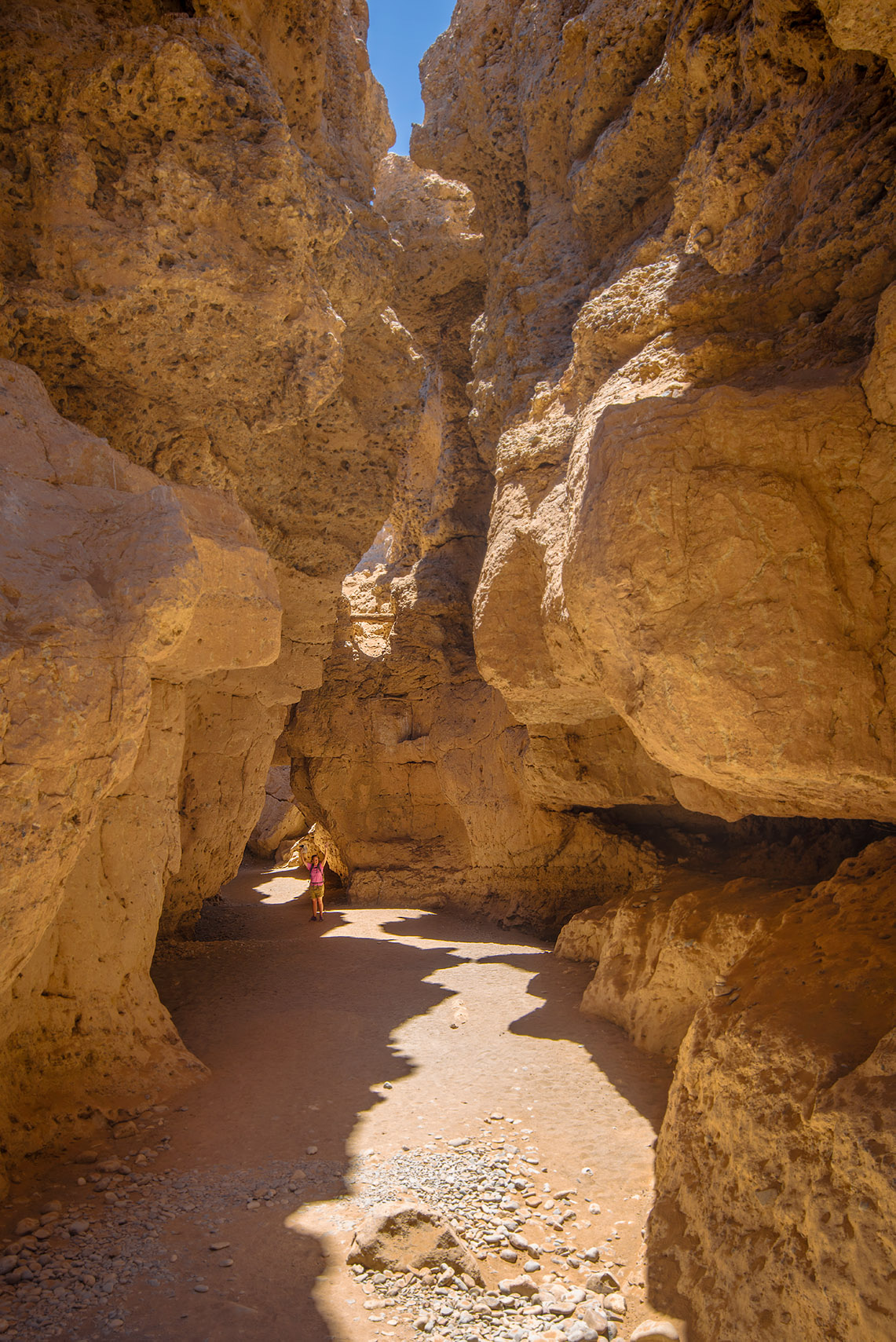 Donna standing, arms outstretched, within the depths of Sesriem Canyon.