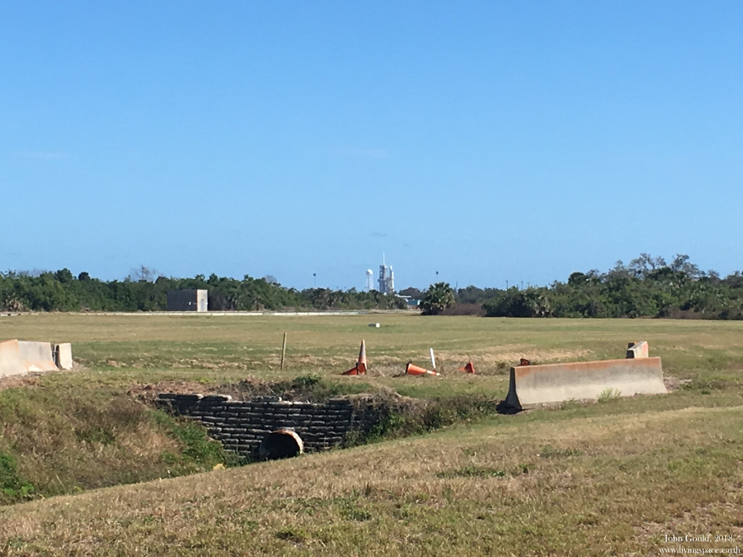 Falcon Heavy sat on LC-39A. The crawlerway cuts through the trees.
