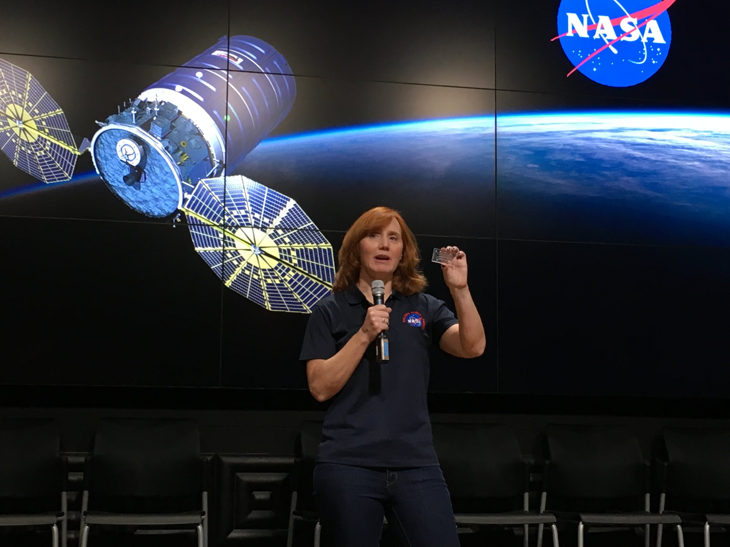 """Siobhan Malany holds a mockup of the """"lab-on-a-chip"""" device carrying her research to the ISS."""