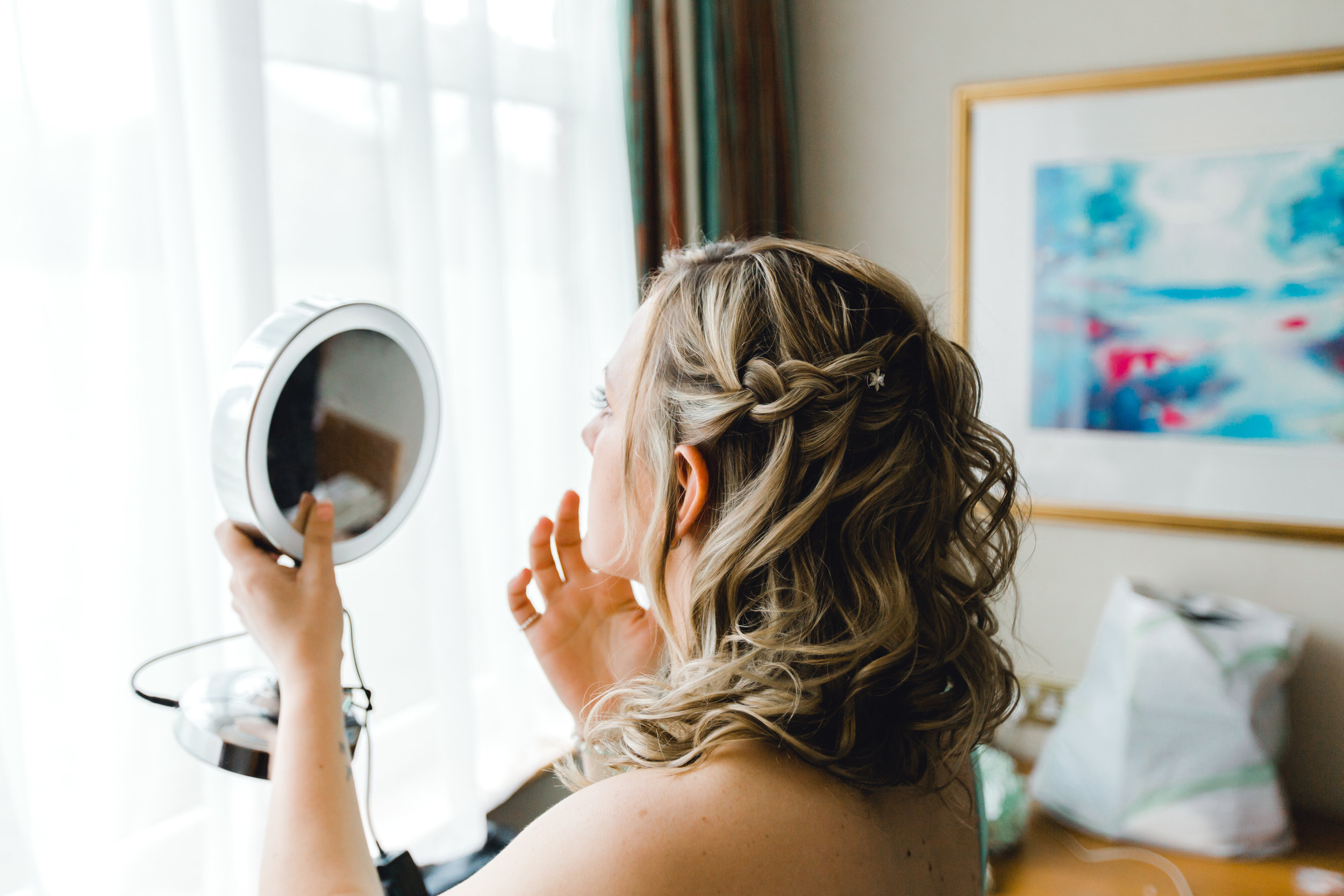 Bridesmaid using mirror to prepare and get ready for the big day