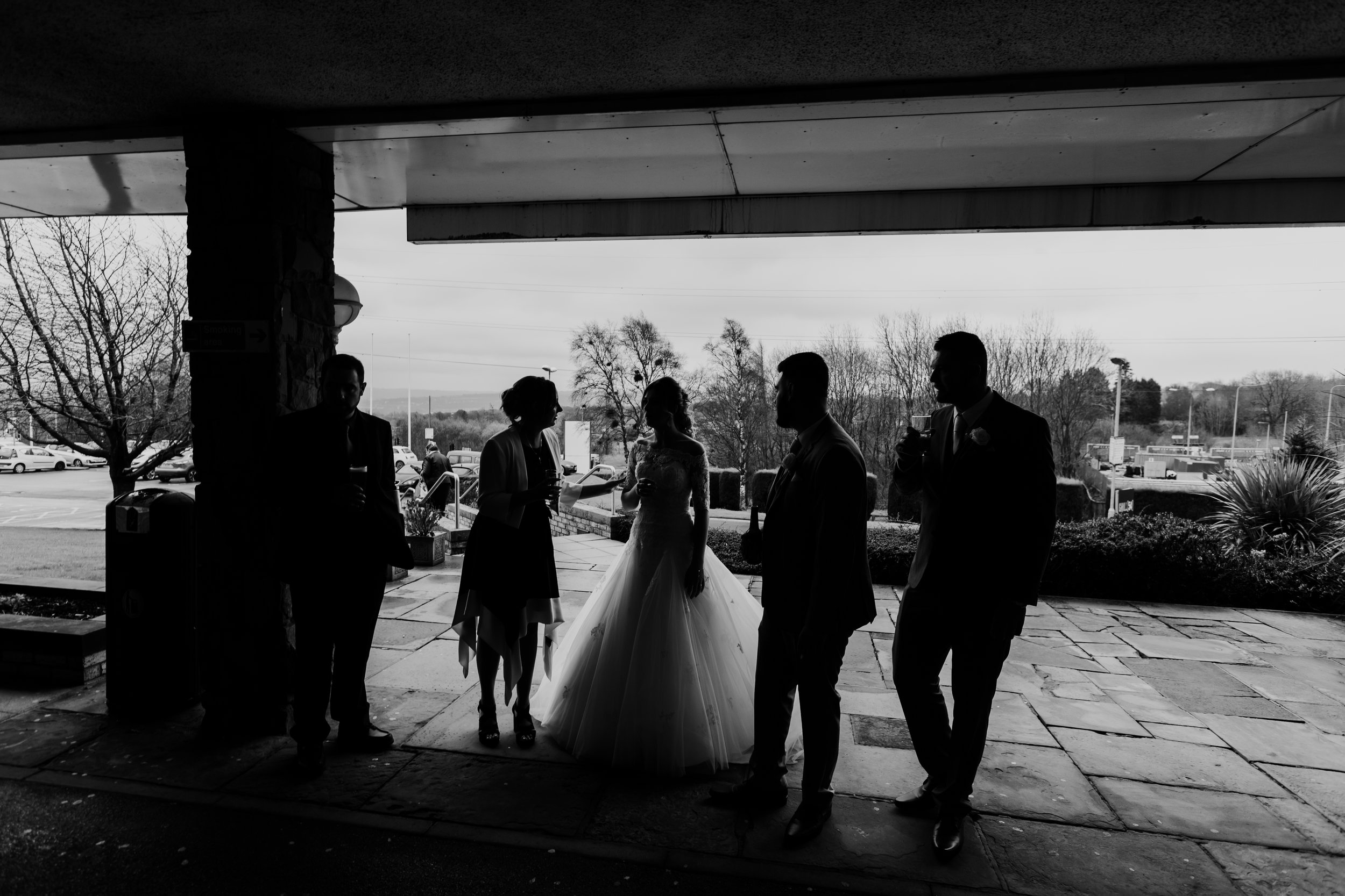 black and white image of bride and her wedding guests after the ceremony