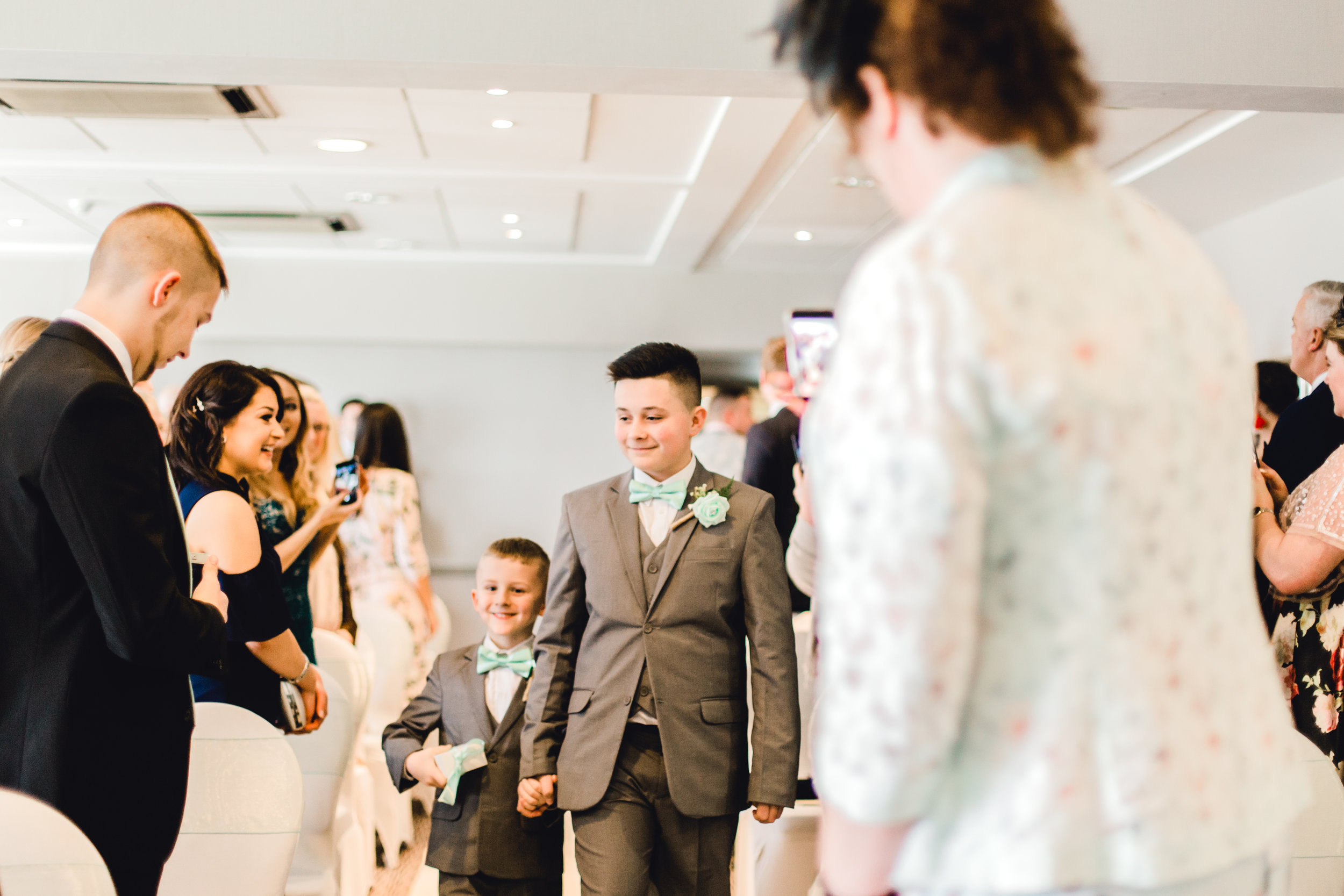 Pageboys walking down the isle before wedding ceremony at cedar court hotel, huddersfield