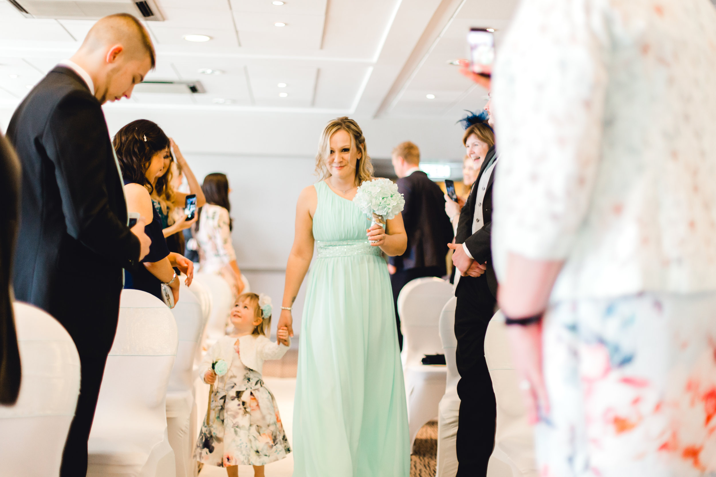 Bridesmaid and flower girl walk down the isle before wedding ceremony