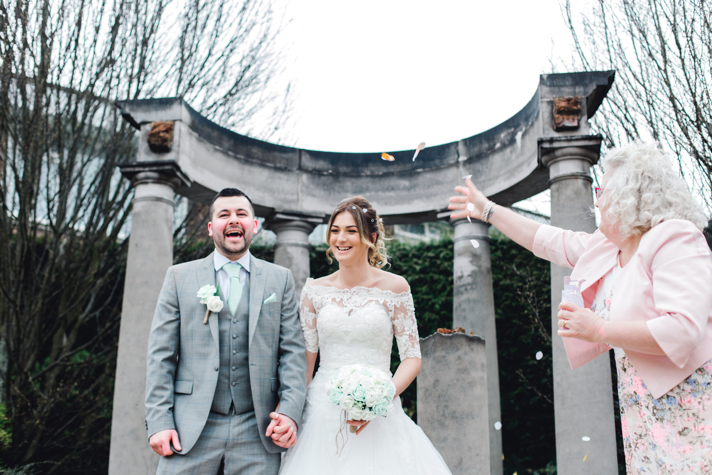 Funny confetti toss over the bride and groom