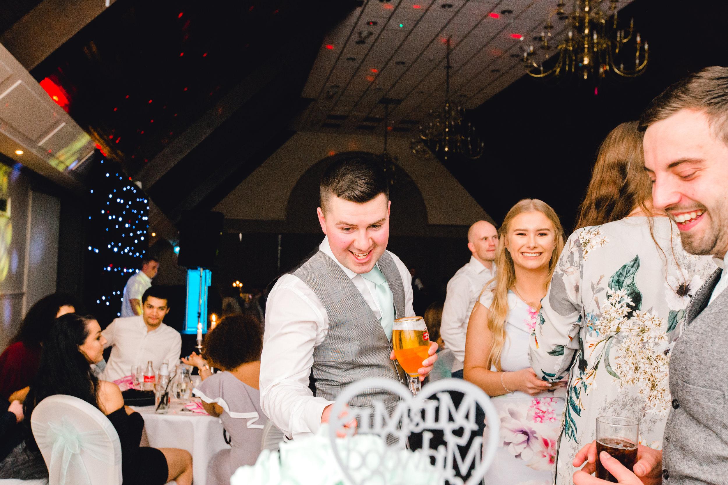 Cheeky best man pretending to cut the wedding cake