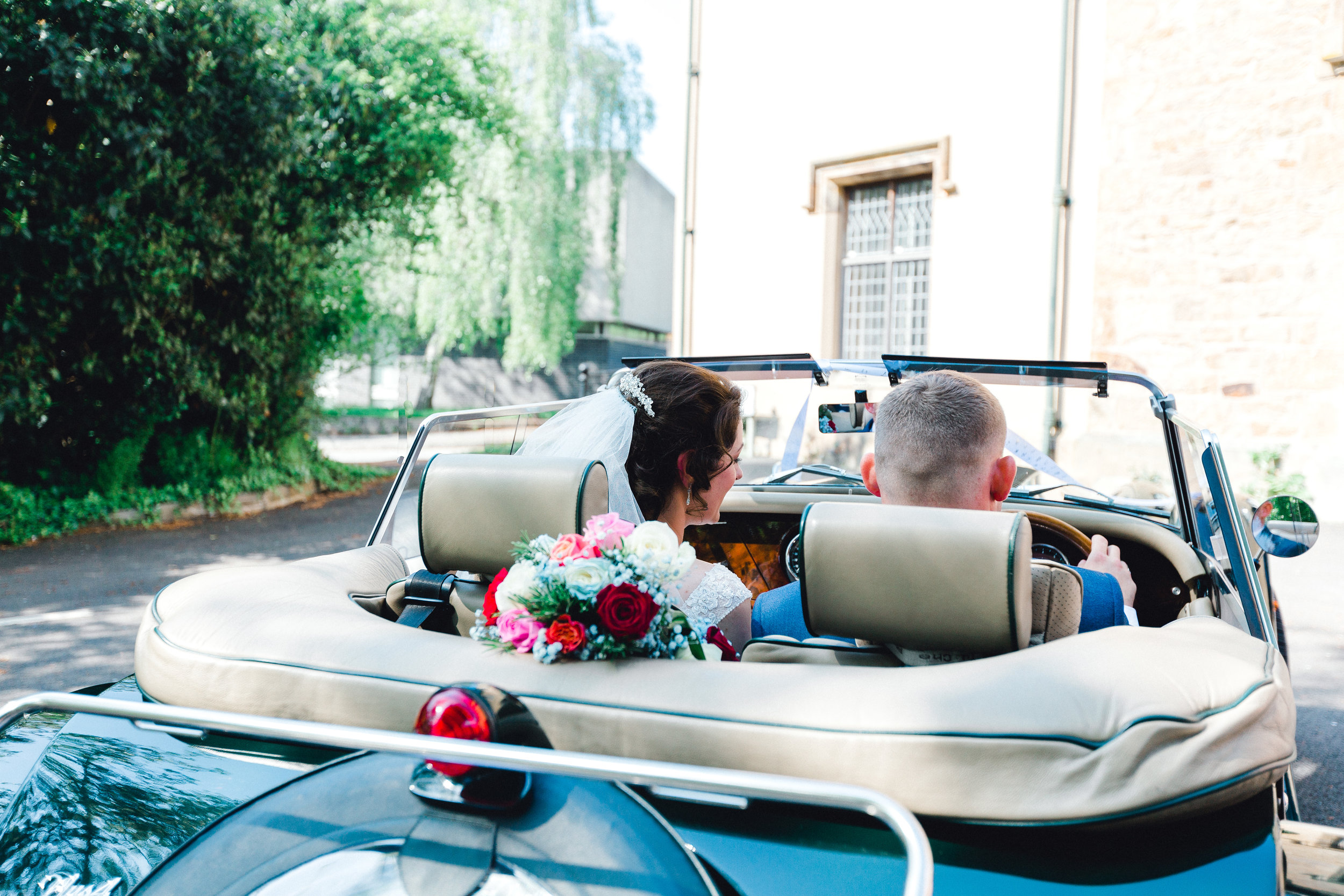 bride and groom about to drive off in a stunning Morgan car