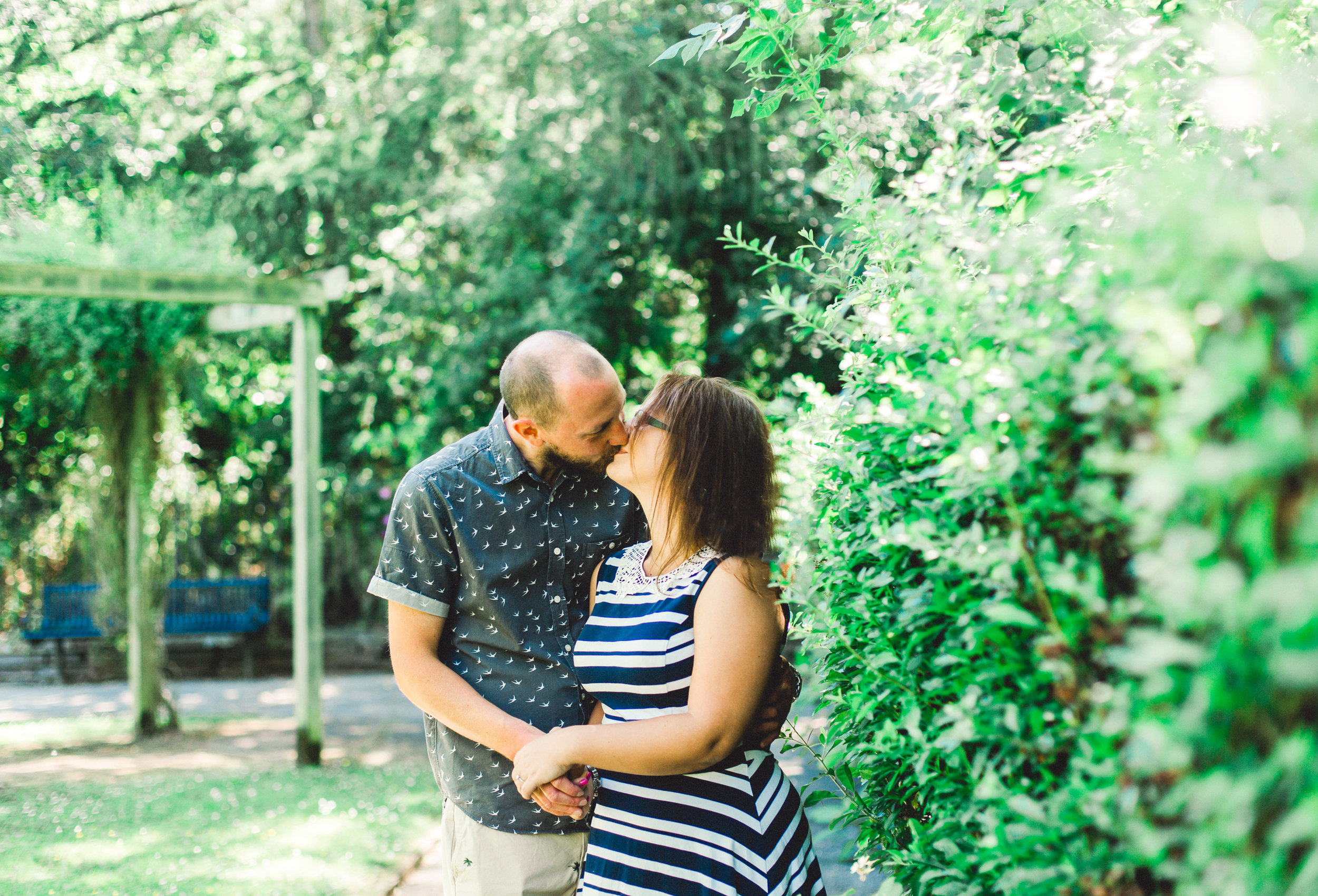 Couple kiss by a row of bushes at Fletcher Moss Botanical Gardens during engagement shoot