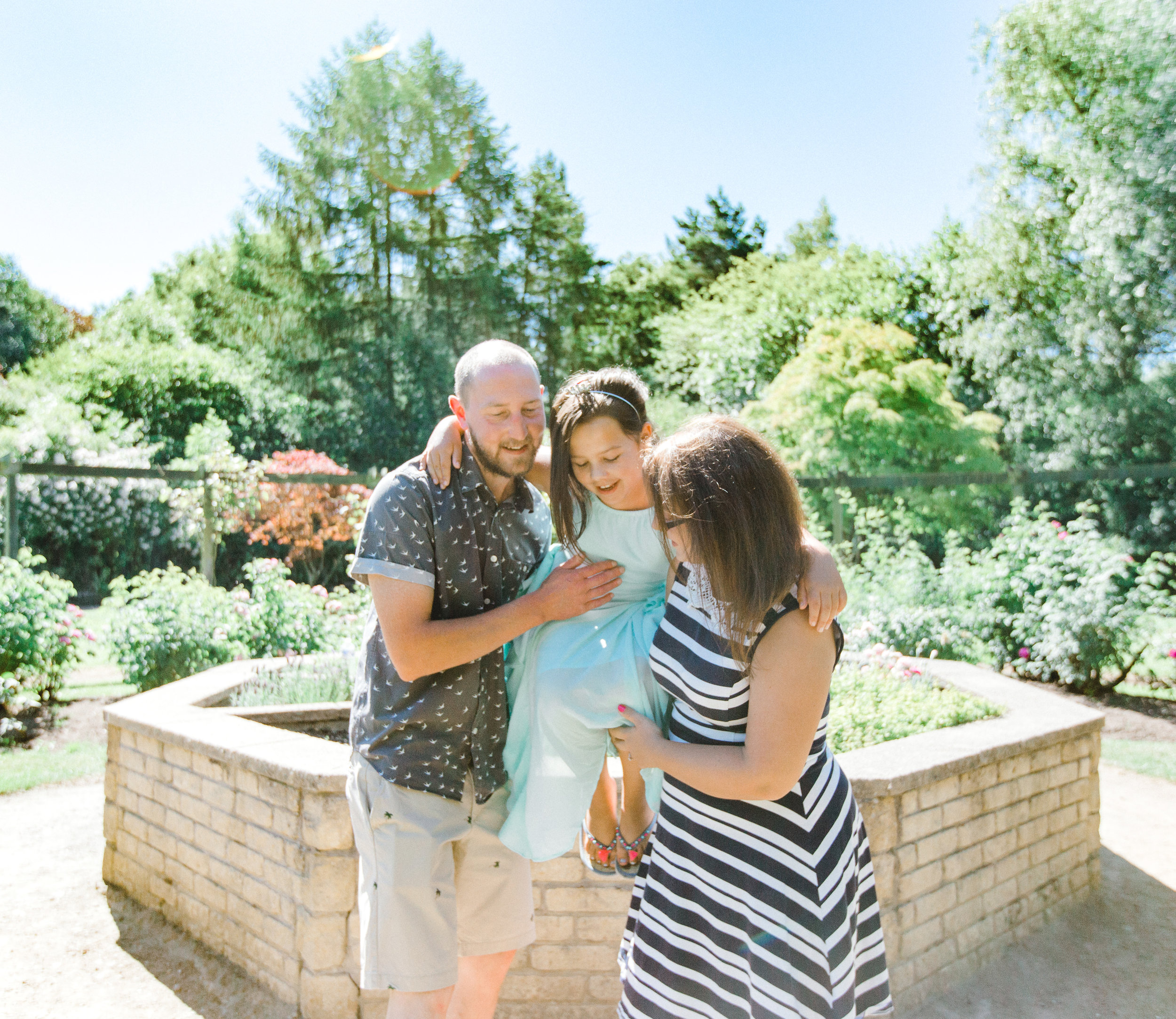 Couple carrying their daughter during engagement shoot at Fletcher Moss Botanical Gardens