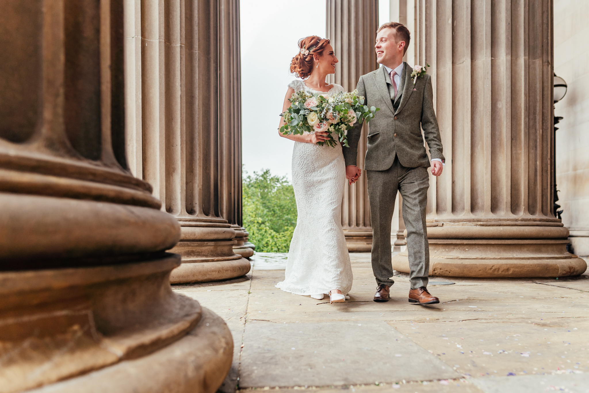 Bride and Groom photograph walking hand in hand through the pillars outside St George's Hall in Liverpool City Centre