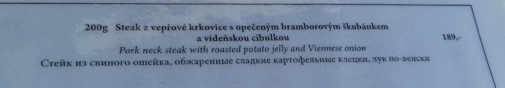 My translation: Pork neck fillet steak with potato cakes and fried onions