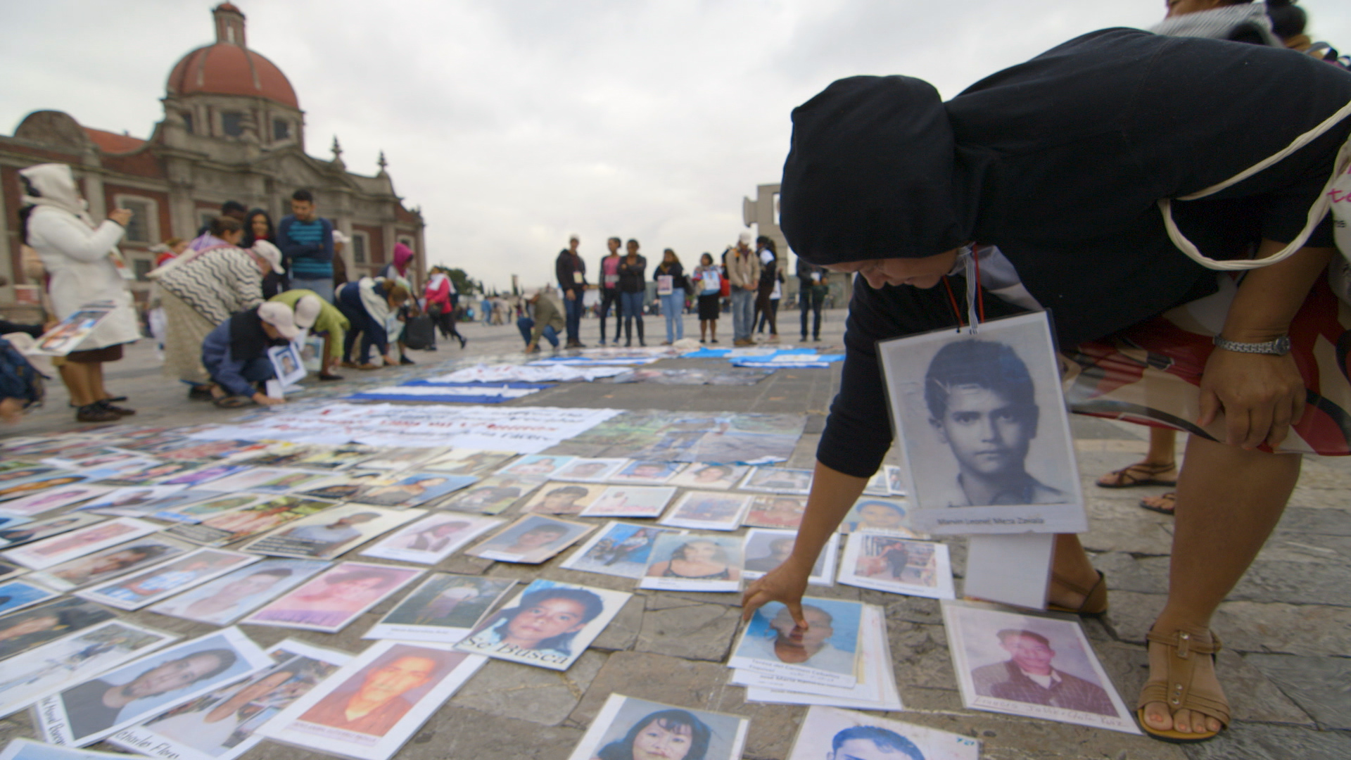 Picking up the pictures of the disappeared out of the Basilica of Mexico City.