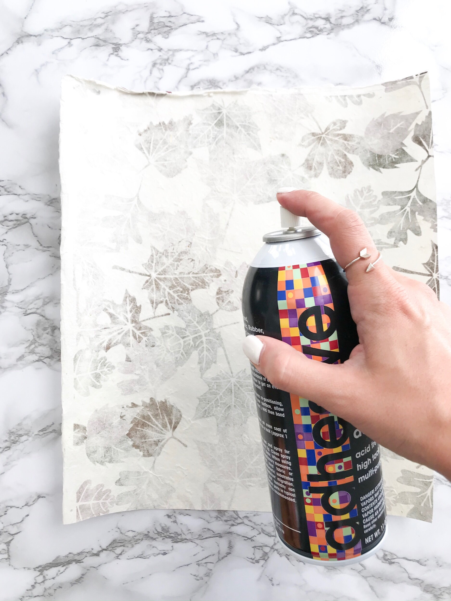 Step Two:  Spray the backside of your scrapbook paper.   NOTE:   We highly recommend doing this outside!