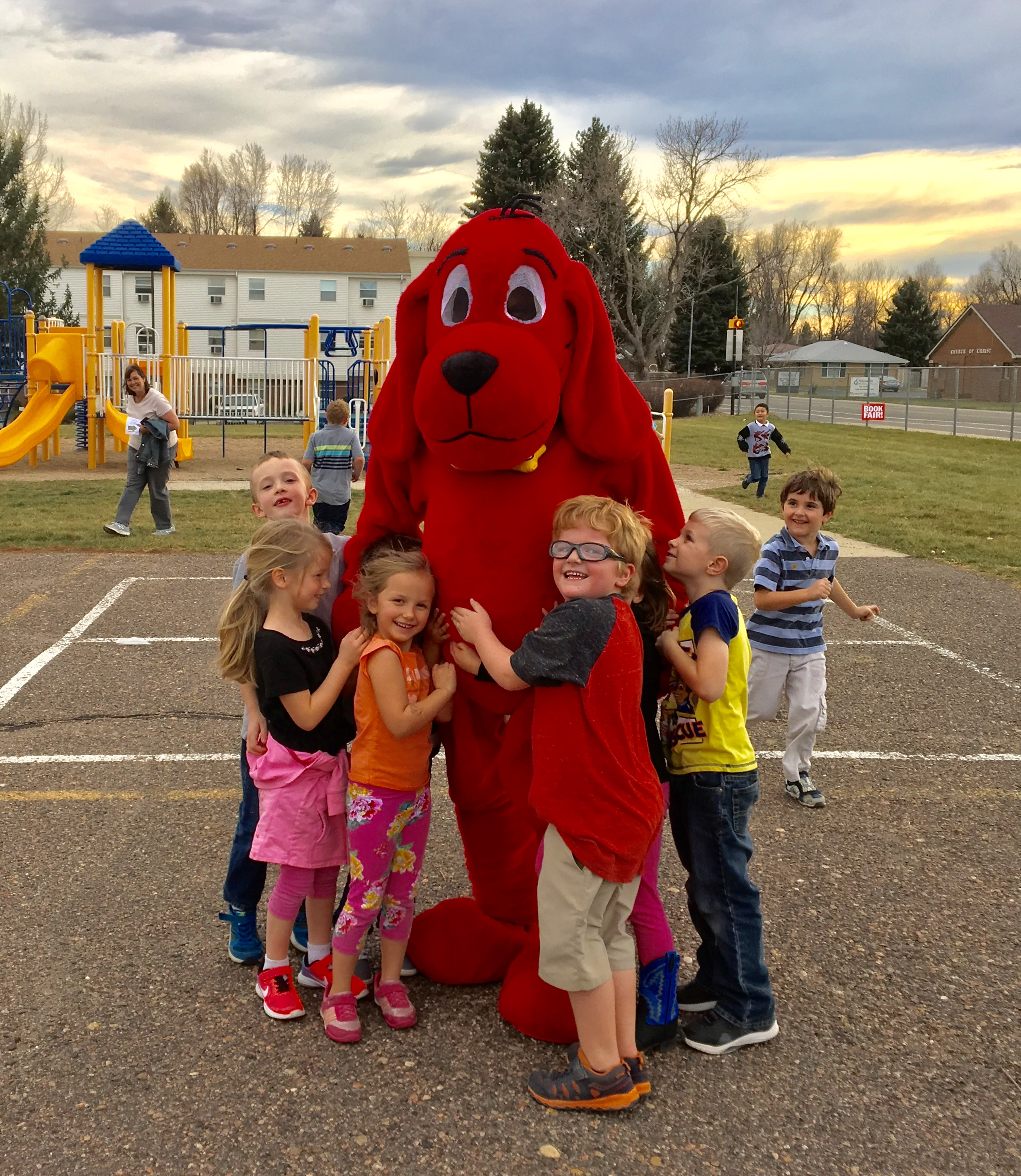 Elementary School students hug Clifford at the PTO-run Scholastic Book Fair.