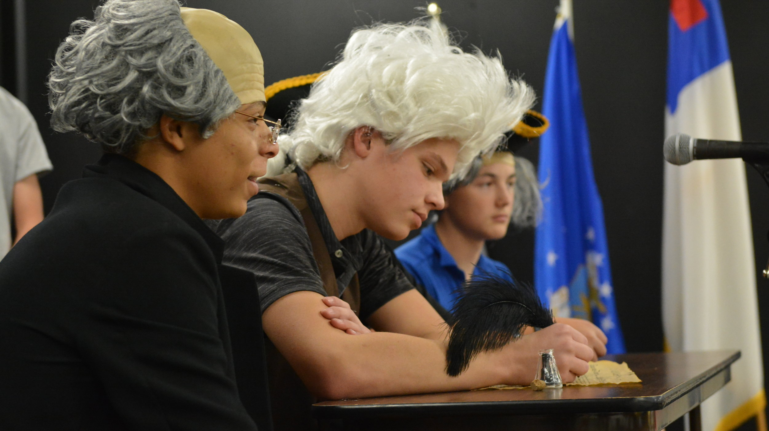 Middle School students re-enact the signing of the Declaration of Independence at the Patriotic Program.