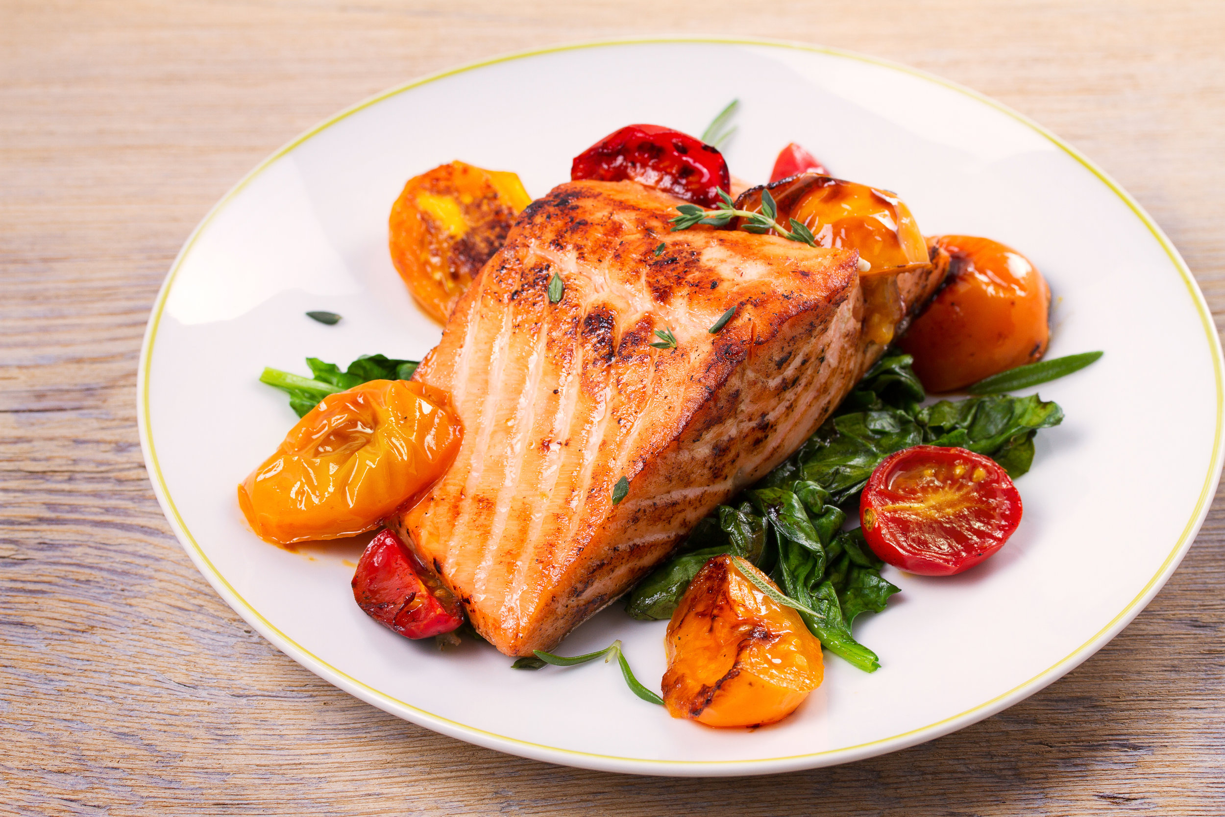 Salmon fillet with spinach and tomatoes on white plate on rustic wooden background.jpeg