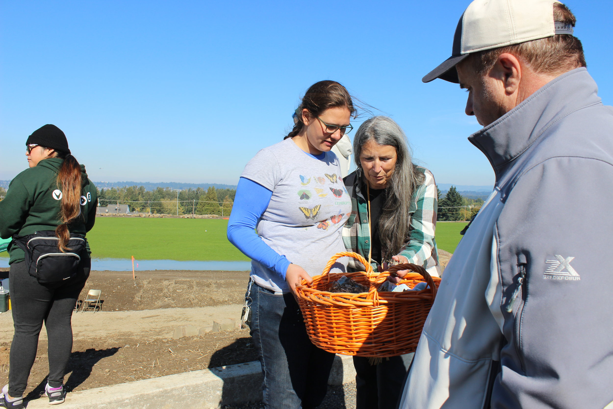 Isabel LaCourse and Judy Bluehorse Skelton pass out seeds after a blessing was given at the Native Gathering Garden Planting in October 2017.