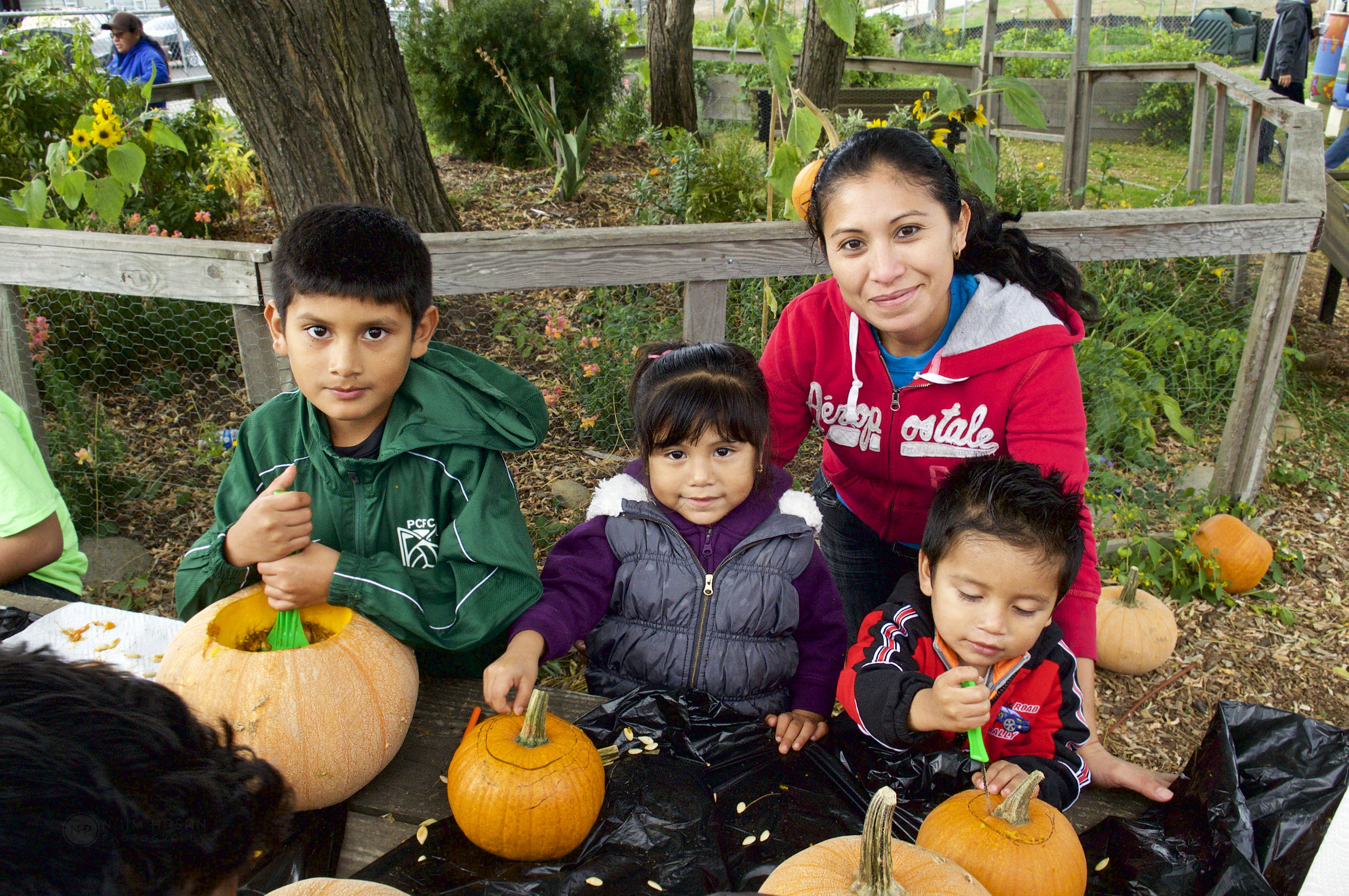 Community Members attend a Pumpkin Carving event at the Community Garden in October 2017. Naim Hasan Photography.