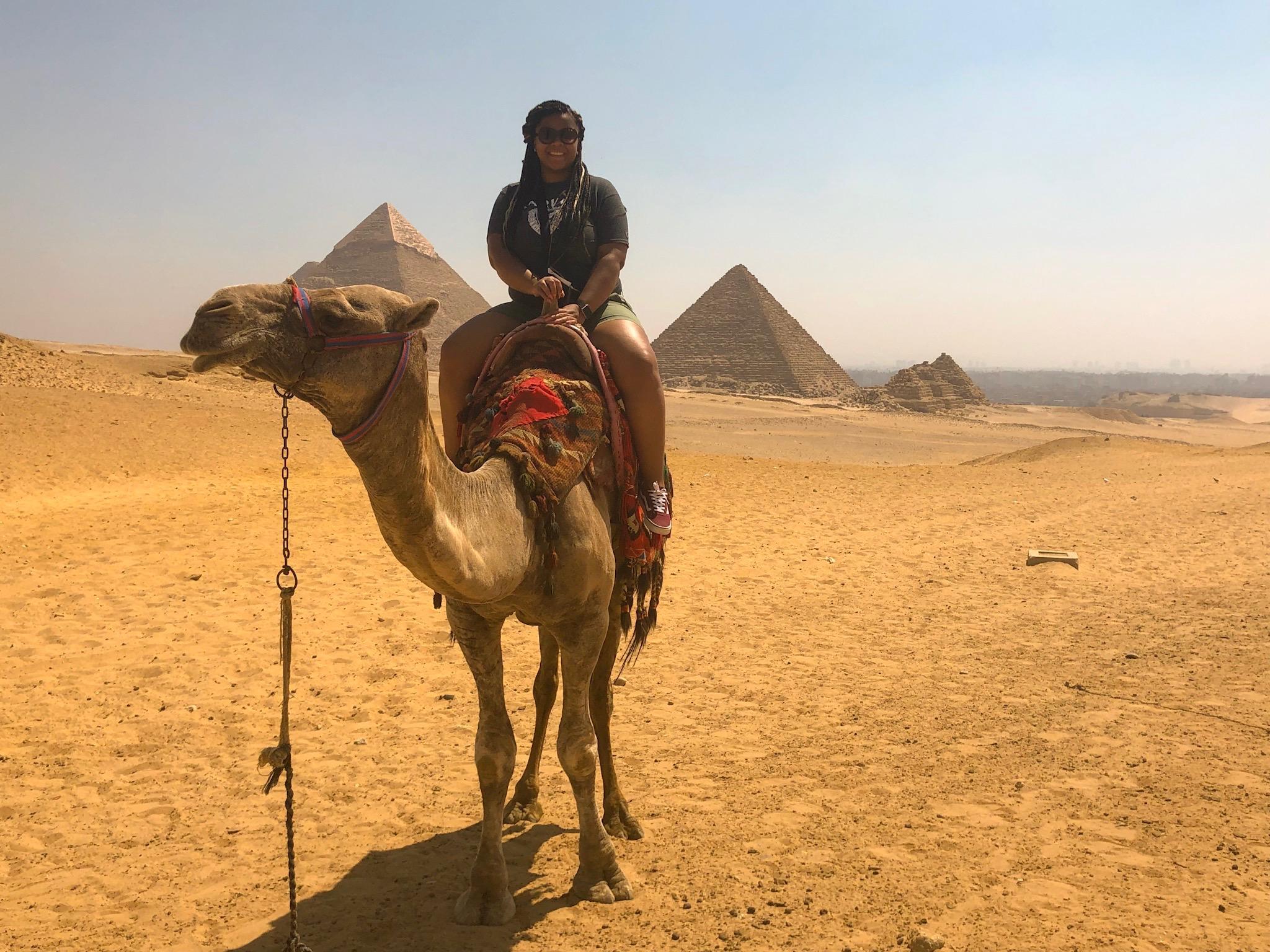 Riding a camel at the Pyramids of Giza.