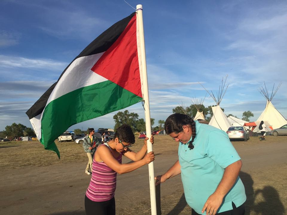 Mark Tilsen putting the Palestinian flag into the ground at Standing Rock camp in Sioux Country. (Photo credit: Friends of Salma)