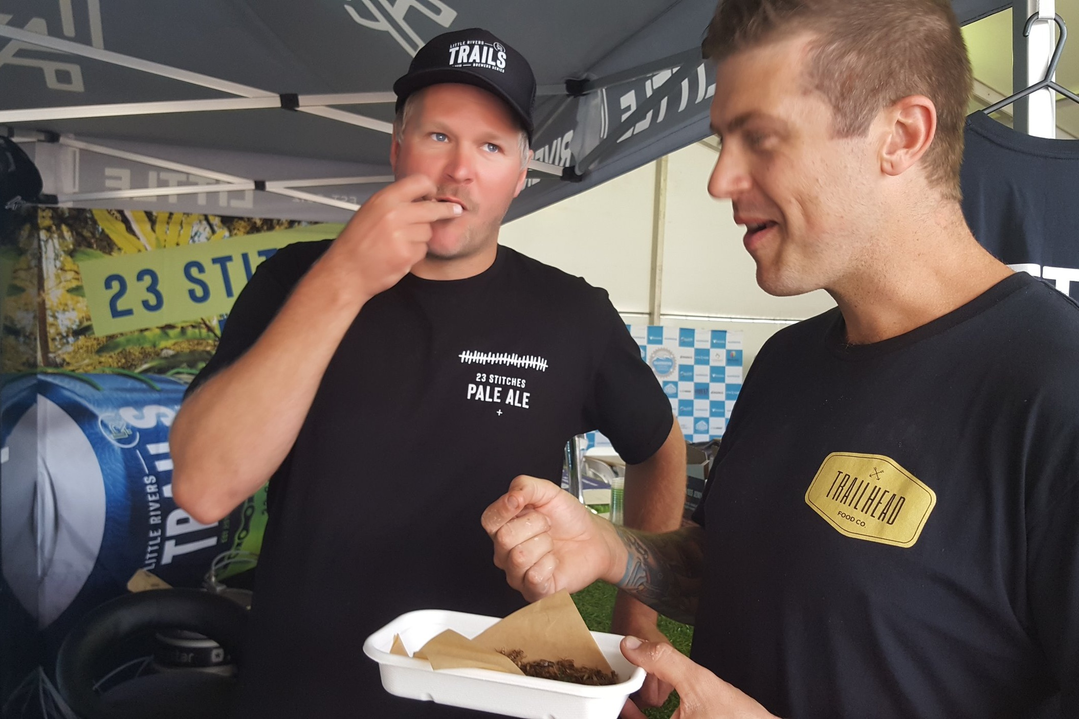 Chris Carins (LRB) and Mark Cornish (Trailhead Food Co) eating crickets at the EWS Derby festival village.