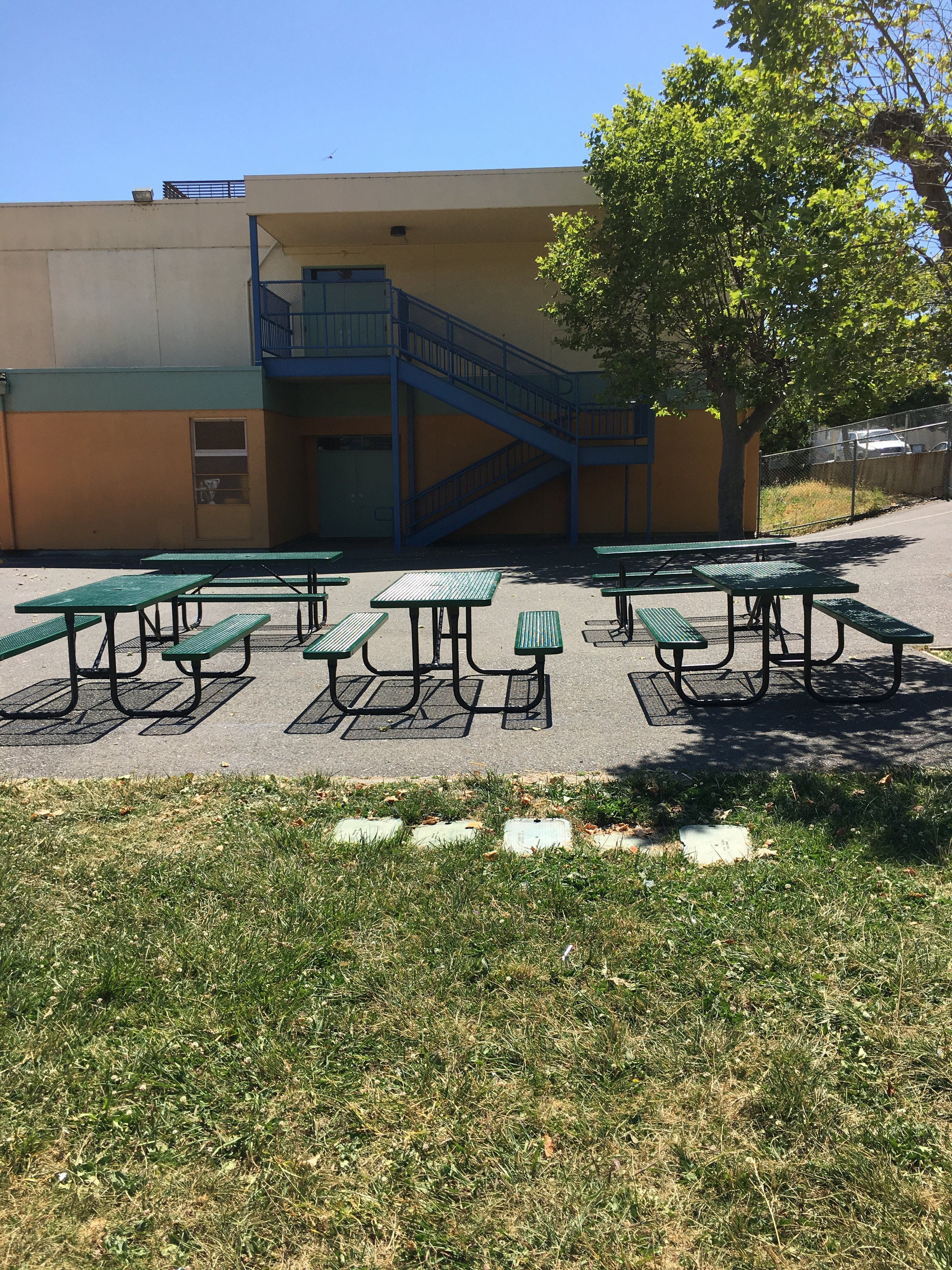 tables in upper yard view to classroom bldg.JPG