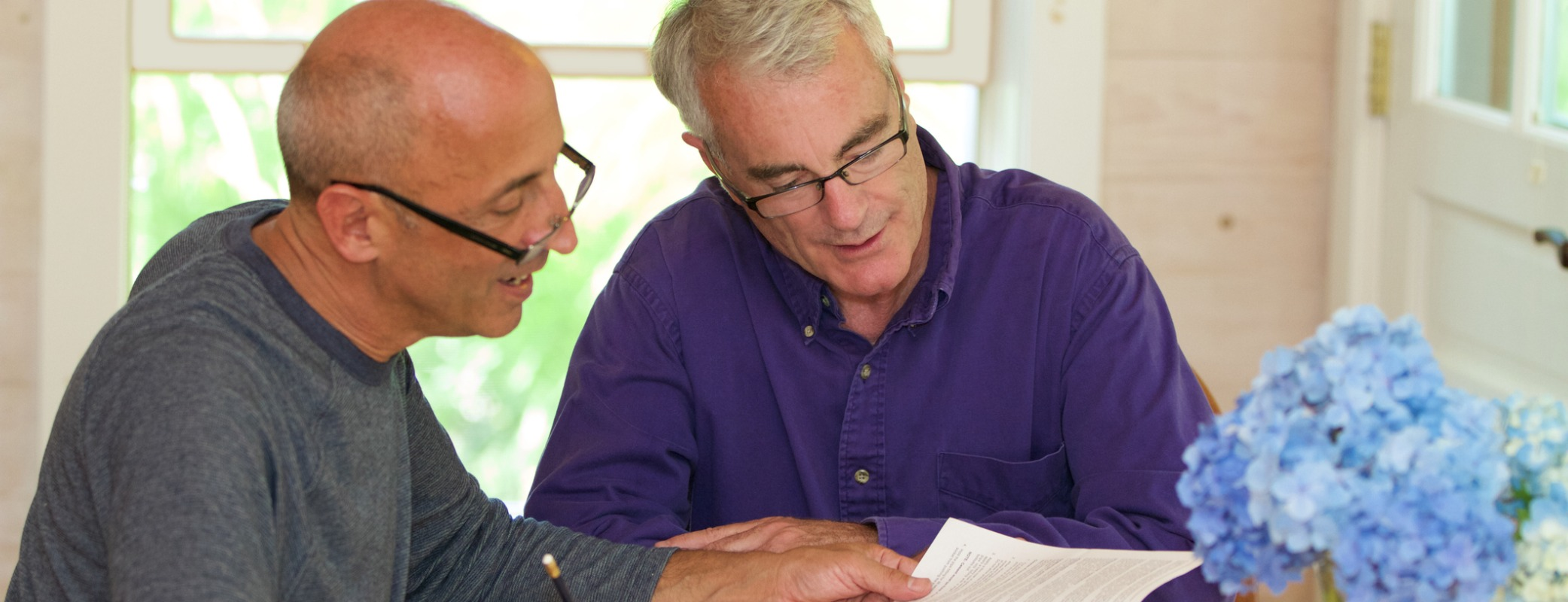 senior-gay-male-couple-working-together-on-financial-documents-picture-id486474484.jpg
