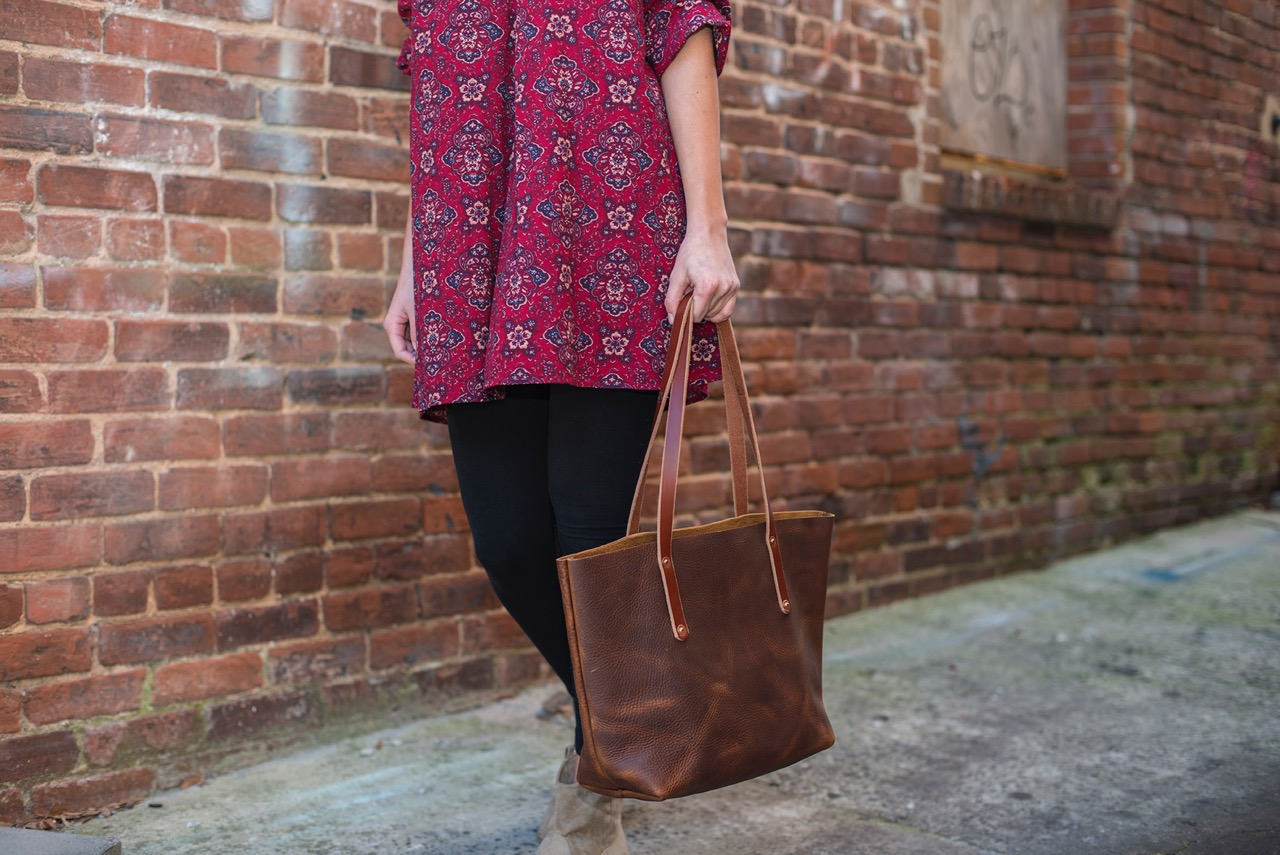 avery-tote-small-saddle-carmen-holding-by-side-low.jpeg