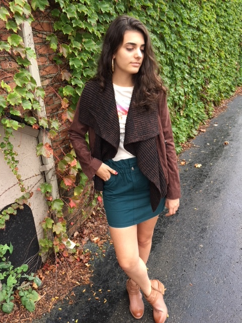 Girl wearing green skirt with Billabong tshirt and brown jacket layered