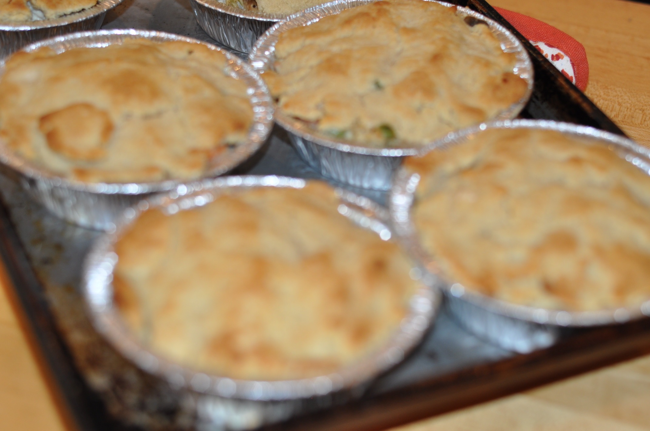 Chicken Pot Pie  INGREDIENTS  4 bone in, skin on chicken breasts 4-5 carrots, peeled and diced 4-5 stalks celery, trimmed and diced 4 T olive oil, butter, or ghee 8 oz sliced mushrooms ¼ cup dry white wine 1 c  cashew cream , plus additional if necessary 1 cup frozen green peas ½ t thyme  Biscuit dough  (awesome recipe from comfybelly.com)  DIRECTIONS  1. Preheat oven to 350. Put the chicken breasts skin side up on a sheet pan and season the chicken with olive oil, then salt and pepper. 2. Bake 35 to 40 minutes until internal temperature (using an instant read thermometer) is 160 degrees. 3. Remove from the oven, allow to cool for an hour. 4. Remove the skin from the breasts and discard. Remove the breasts to a plate. 5. Tilt the baking sheet, catching all of the liquid broth and fat that accumulated while the chicken was cooking. This stuff is delicious and will make your pot pie taste better. 6. When the chicken is cool, shred it with your hands. Save the bones for chicken broth. 7. Chop the chicken into smallish pieces and put into a very big bowl. 8. In a large skillet over medium heat, heat 2 T butter, ghee, or olive oil. Add the celery and carrots and saute until softened but not mushy. Salt and pepper them while they're cooking. 9. Add to the bowl with the chicken. 10. In the same skillet, heat 2 tablespoons more oil or butter and saute the mushroom slices until they give up their juice and become softened. Then pour in the wine and cook that down. 11.Add to the bowl with the chicken. 12. Now stir in the cashew cream, the reserved chicken fat/broth, and salt and pepper. 13. Sprinkle in the thyme and frozen peas. Add more cashew cream if it's not creamy enough. 14. Stir everything together really well. 15. Mound the mixture into individual foil pie pans (makes for easy freezing of lots of servings). 16. Break off a ball of biscuit dough (a little bigger than golf ball size) and work it with your hands to flatten it, and then put this on top of each little pie (it doesn't have to be perfect and it's okay if it doesn't completely cover it). 17. Put each pie onto a baking sheet and load the whole pan into the oven. Bake for 20 minutes or until the biscuit dough is puffed and golden. 18. Enjoy right away or cool and freeze for later.  Makes 8-10 pies, depending on the size of pie pan you have.