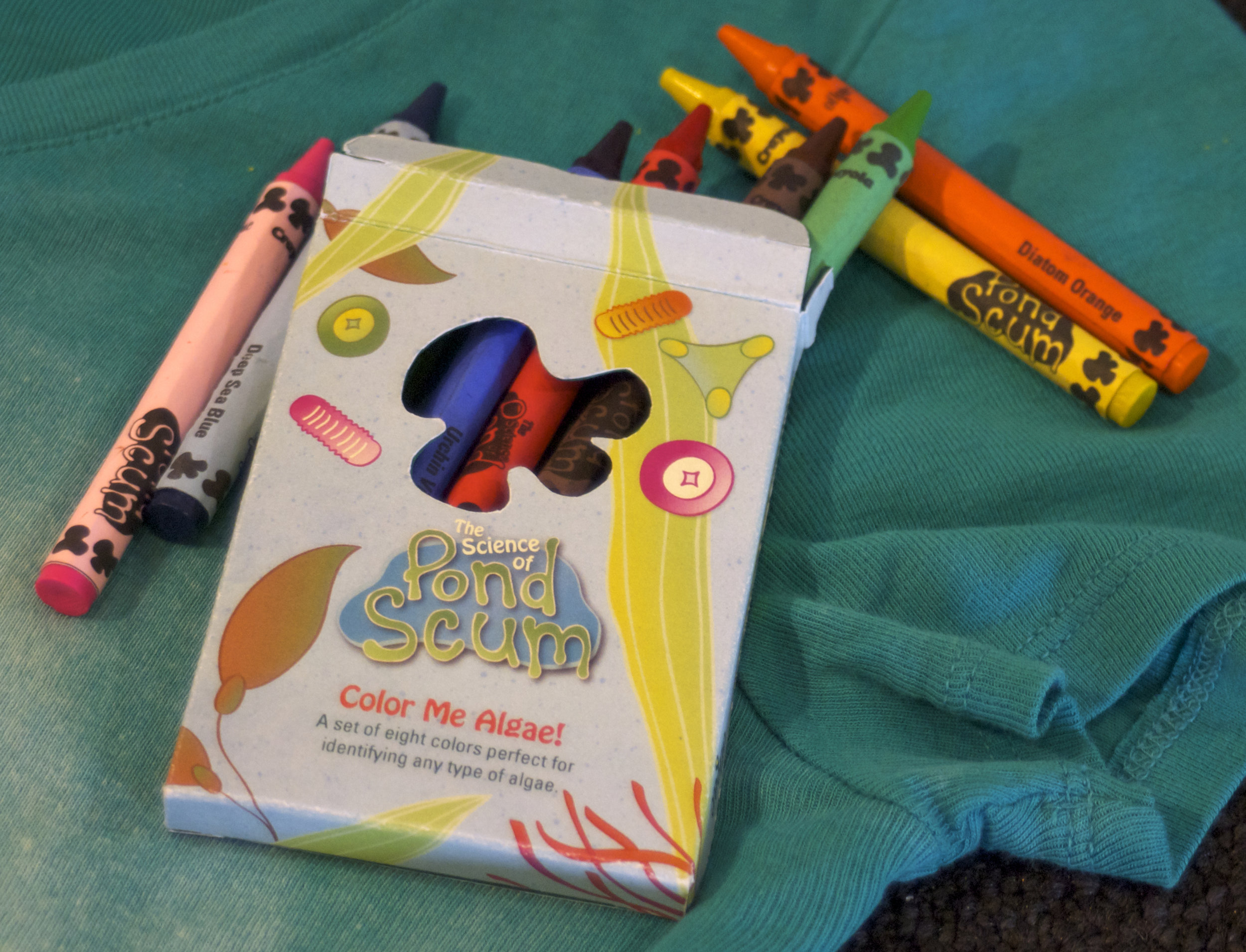 A custom set of crayons to give away to kids during the SoPS lecture, featuring related art on the box, a cutout window of the mascot Al, and specific color names, relevant to the information they've learned.