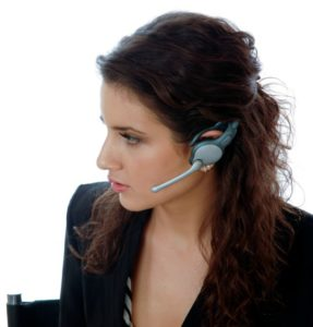 Brunette female telephone agent answers call with concerned look on her face.