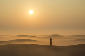 A lone person stands in a the desert sand dunes at sunset.