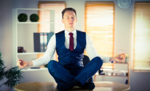 Man meditating in lotus pose, wearing a blue suit on his office desk.