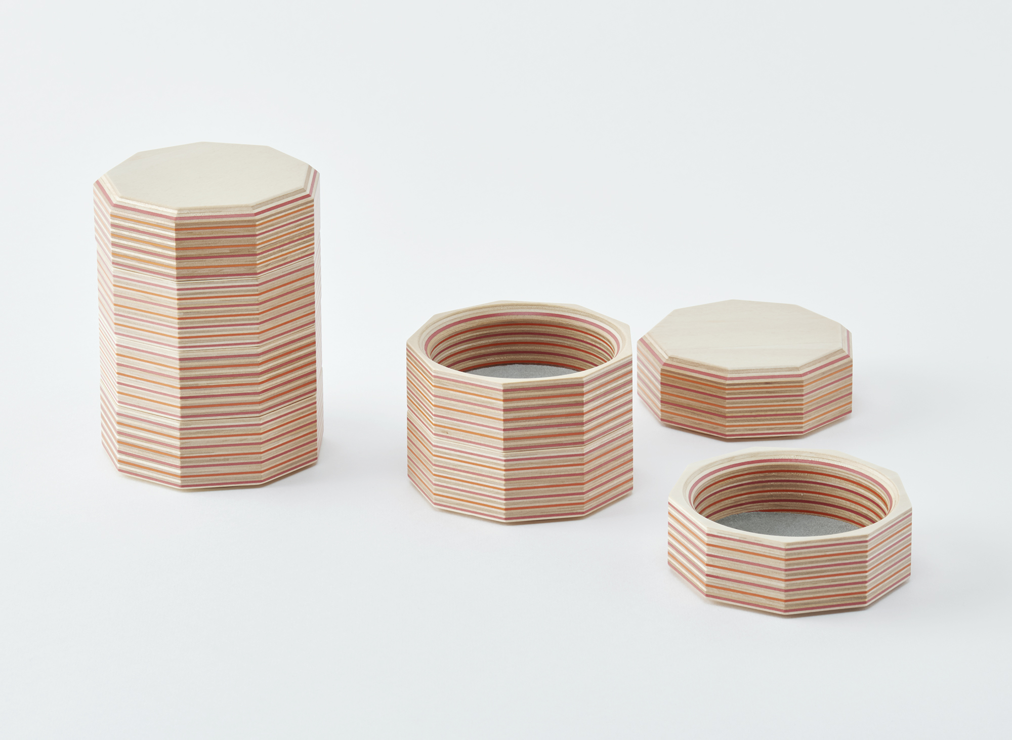 Curator: a nondescript everyday tray made with outstanding craftsmanship and material - The trays feature rhythmical forms and are designed to be stacked, resulting in towers with a striped pattern. It is made with paper-wood, which is a plywood that has colourful and beautiful cross section born of an innovative method involving the lamination of coloured recycled paper and wood grown in Hokkaido.