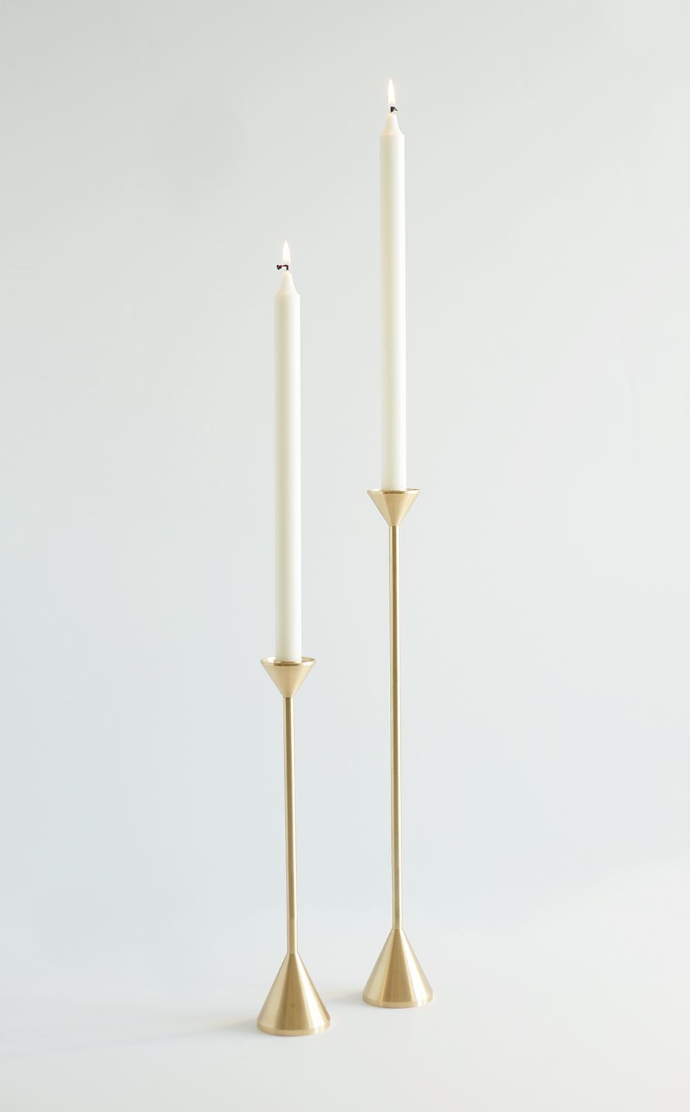 "Curator: it did not attempt to ""outshine"" the candle but announce it's presence with it's own quiet beauty. - The tall, simple design of this candle holder adds a modern twist to a classic object and creates an elegant accent in any living or dining room. Machined from solid brass, it demonstrates the impressive weight of brass and the precision of the tool used to form it."