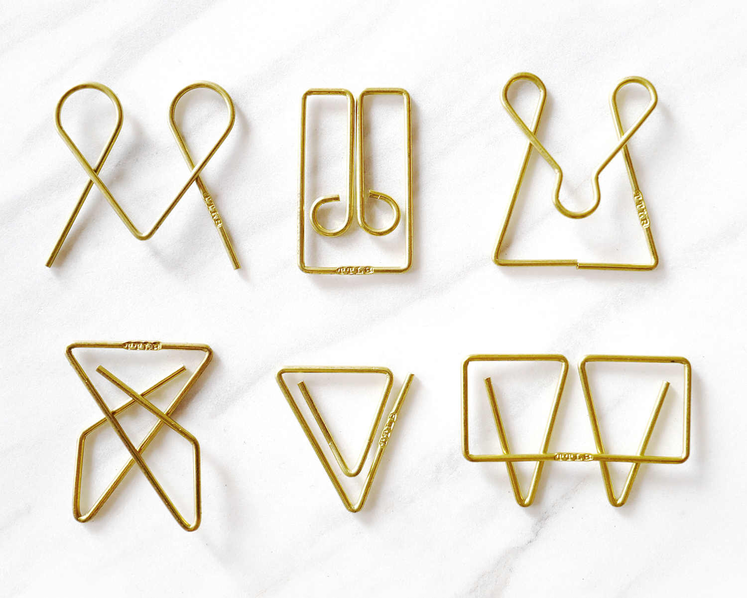 Curator: example of how better design can elevate even simple and basic items around us. - These brass paper clips are perfect for keeping documents and important sheets of paper in check. Smart in design, these binder clips allow you to see through to the paper.