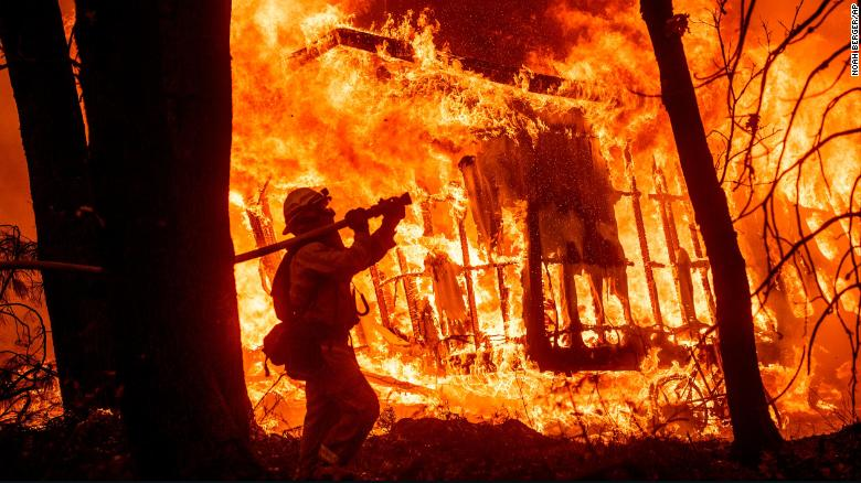 image from CNN / Firefighter Jose Corona sprays water as flames consume a house in Magalia, California.