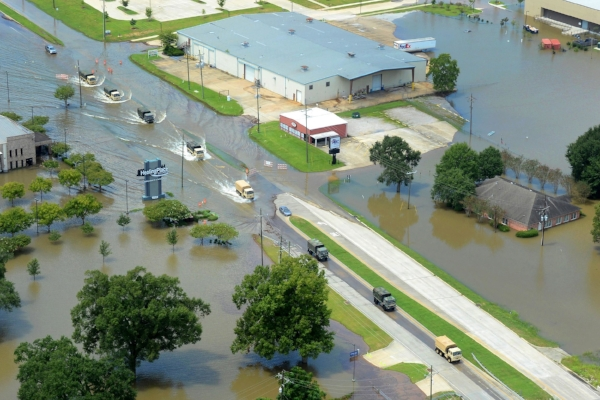 US Army tactical vehicles transport supplies along a highway in support of Louisiana flood relief efforts