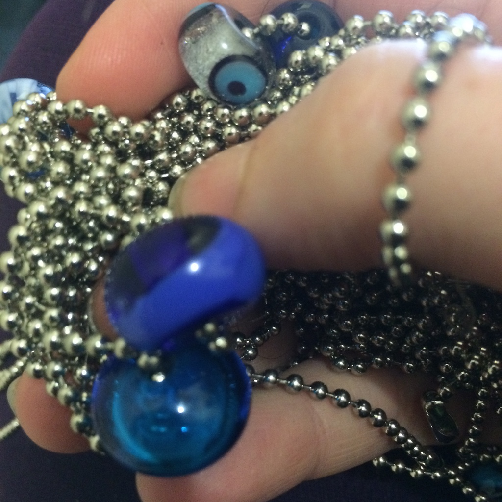 Ruti Regan stimming with blue glass beads on a chain