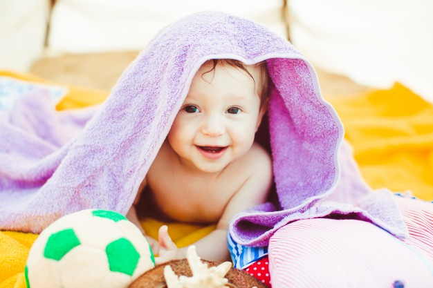 toddler-boy-lying-covered-with-purple-towel_1304-4148.jpg