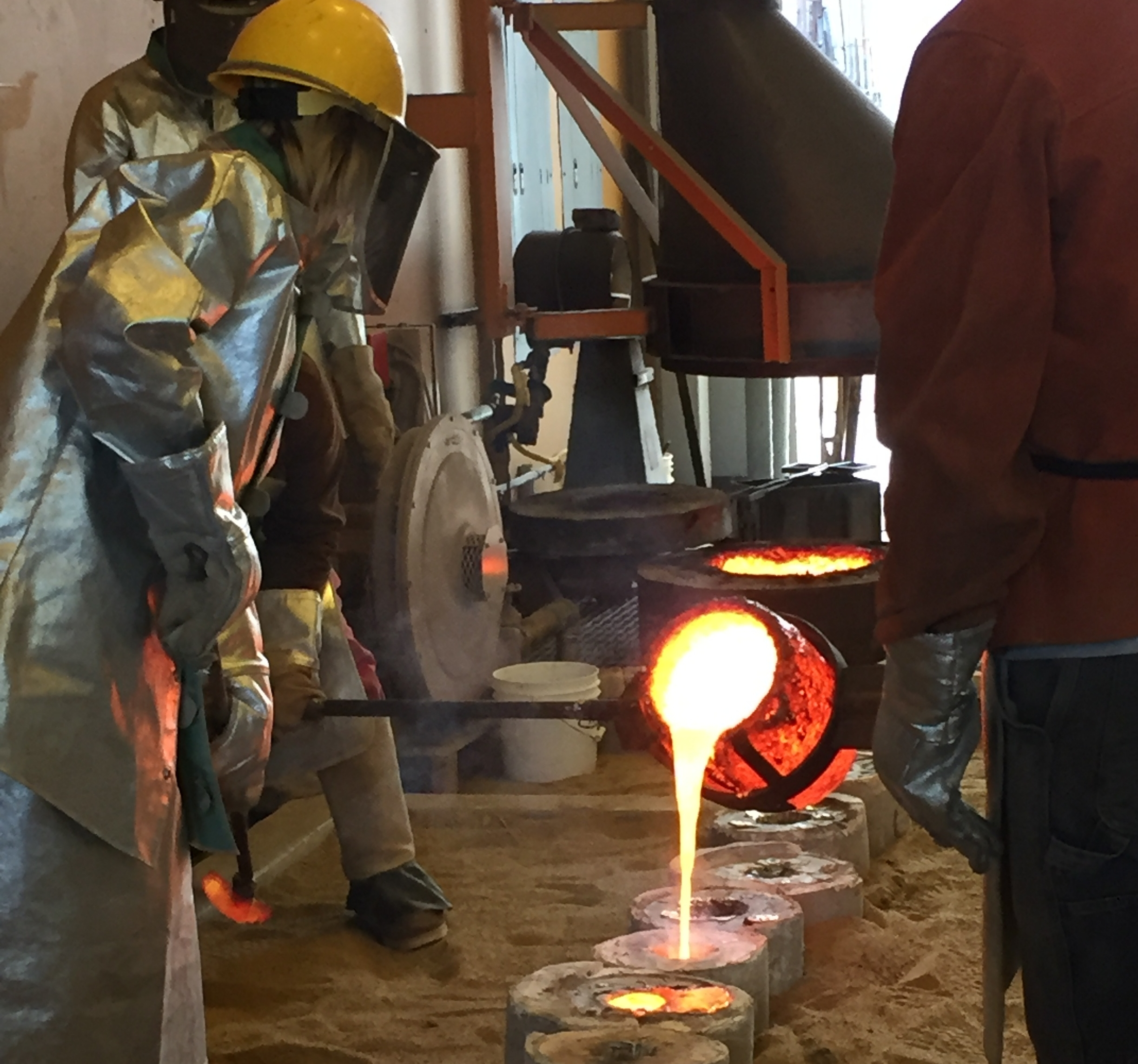 The pouring of molten bronze in hot flasks.
