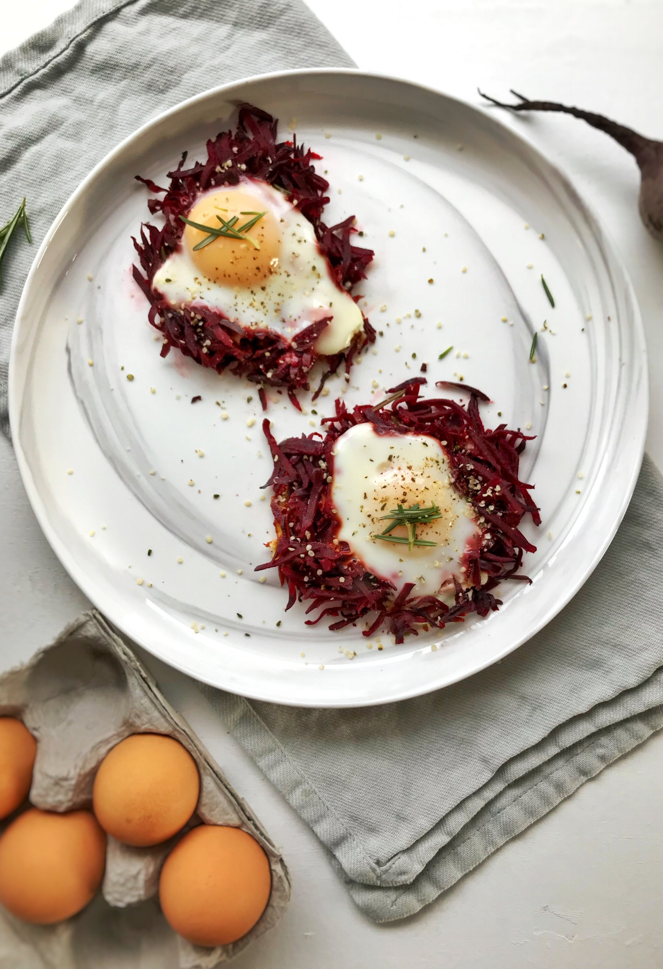 Red Beet Egg Nests - Ingredients:1 clove garlic1/4 cup onion2 small beets/ 1 large beet2 eggsRosemary, salt, pepper & hemp hearts to garnishDirections:Wash & spiralize 2 smaller beets or 1 large beet. I have a hand spiralizer, which is harder to use with smaller foods, but experiment to see what works best for you. Heat a skillet with extra virgin coconut oil, 1 minced garlic clove and the onion. After a minute of sizzling, add the spiralized beets to the skillet and mix thoroughly. Cover, stirring occasionally for around 10 minutes.When beets are nearly cooked (will be soft in texture, but not too soft), add fresh rosemary, salt and pepper. Position beets into two